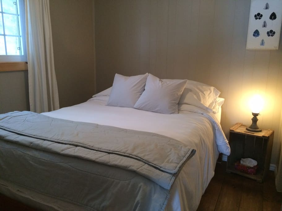 Comfortable queen size bed with lots of fluffy pillows / Un grand lit avec plusieurs oreillers.