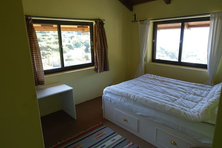 Guest bedroom 2. With views to the backyard pool and across Sarangkot Valley.
