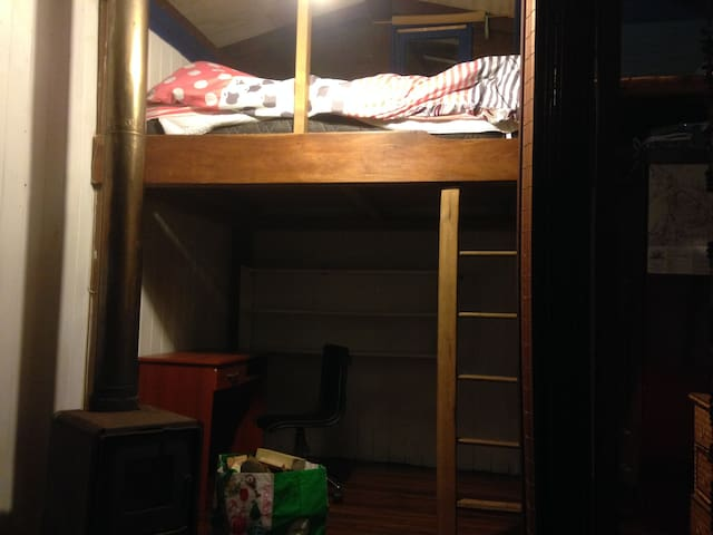 La cama matrimonial esta en altura, debajo escritorio y estantes