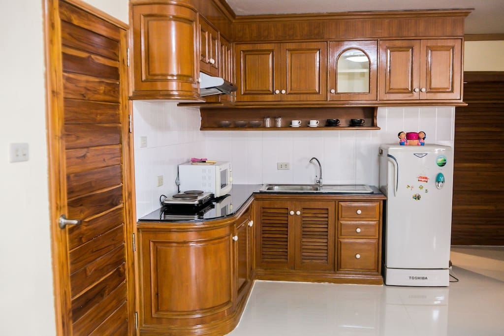 This kitchen is fully stocked with everything you could need to cook with. It has a microwave, stove, cooking fan and basic spices.