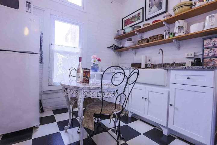The small modern kitchen where a bottle of wine, homemade bread, and breakfast scones are left for you to enjoy.