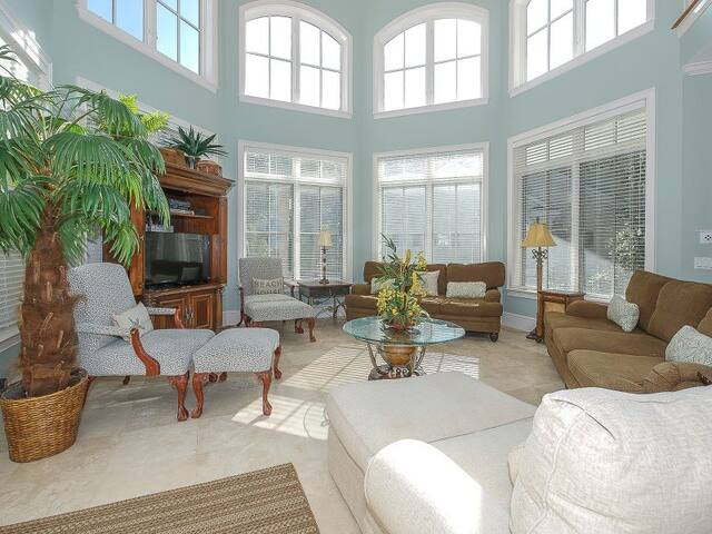 The living area is spacious, high ceilings, open floor plan and plenty of seating for everyone. You can see the private pool from the living area. Off the living area is a 1/2 bath, 2 bedrooms with baths, the kitchen ,dining area & the laundry room.