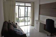 Escritório  com sofá cama e porta com acesso a varanda que dá na sala