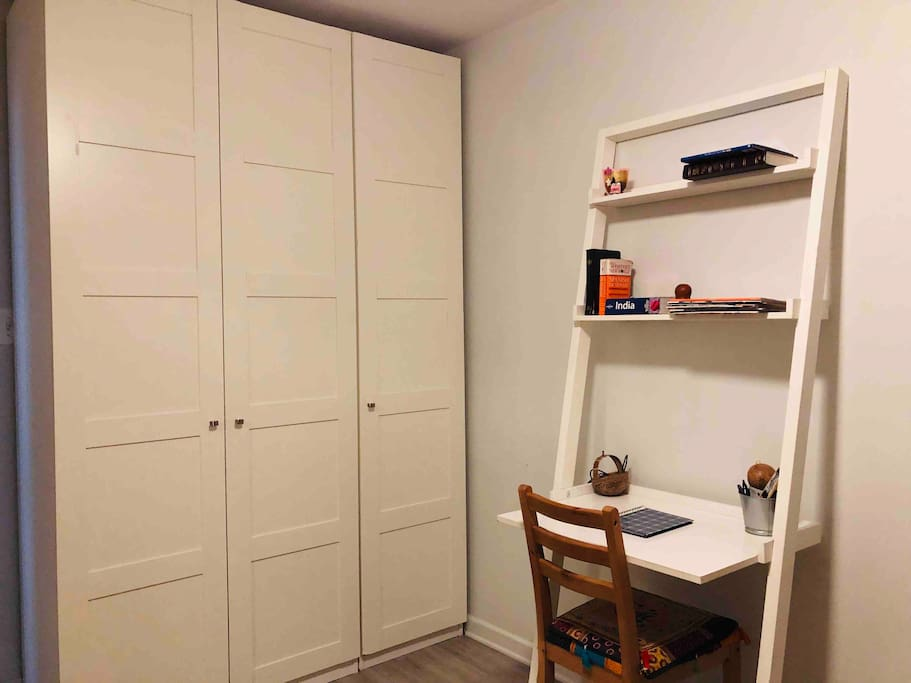 Leaning desk/workspace along with ample closet space and extra linens