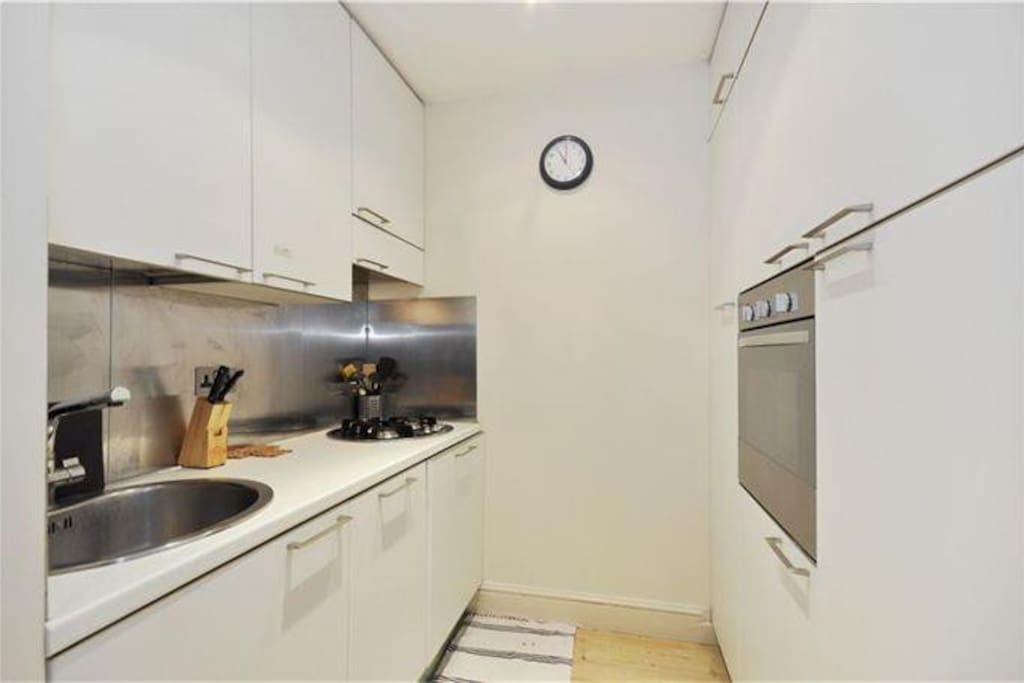 Kitchen, with dishwasher, oven, fridge, extractor fan.