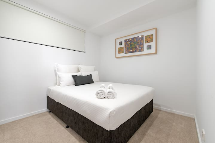 The second bedroom also features a queen-sized bed, topped with crisp white linens to ensure a good night's sleep.