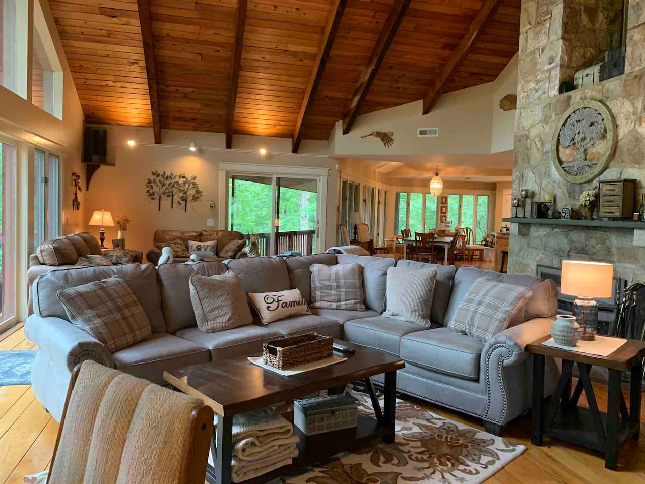 Great room offers two seating areas, a wood stove, a table for 4, and beautiful views.