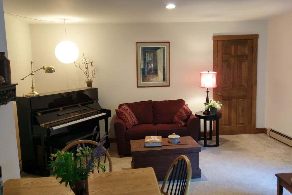 Pitch perfect Yamaha piano in sitting area with TV.