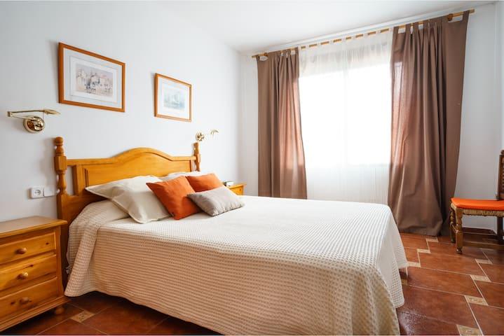 Dormitorio principal. La ventana da a la parte trasera de la terraza. Tiene persiana. La habitación es amplia y caben 2 cunas. Tiene 2 mesas de noche y lámparas de lectura regulables.