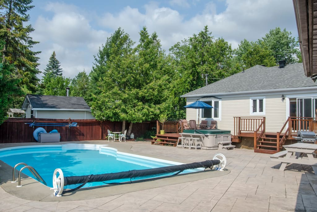Backyard from the fence with pool, deck, hot tub and BBQ