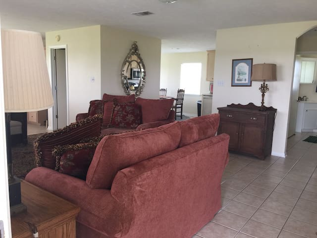 The living room has three couches and a recliner.