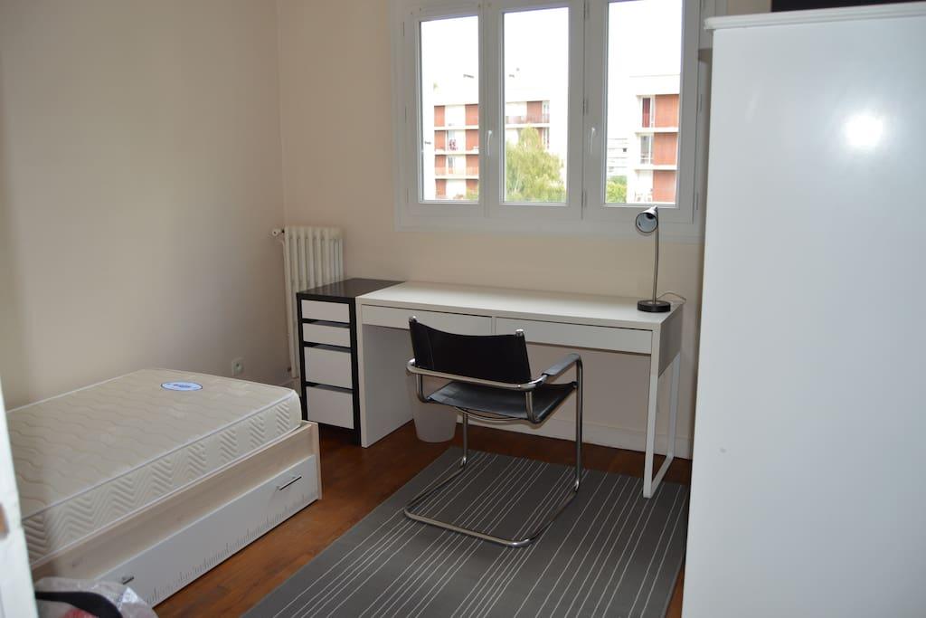 Chambre avec lit simple (bureau, fauteuil, lampe)