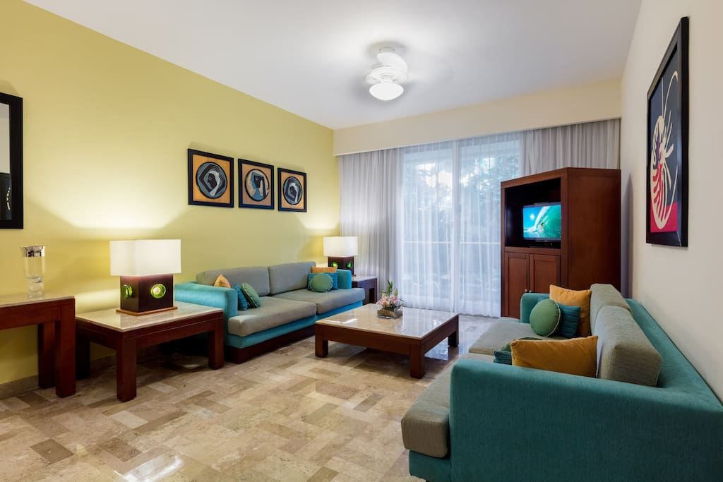 The living room features a large flat screen TV with satellite cable.