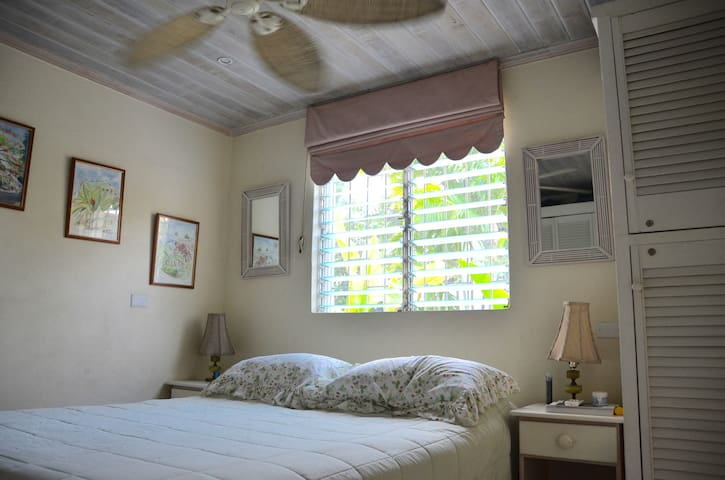 Queen-sized bed in an air conditioned room with ceiling fan