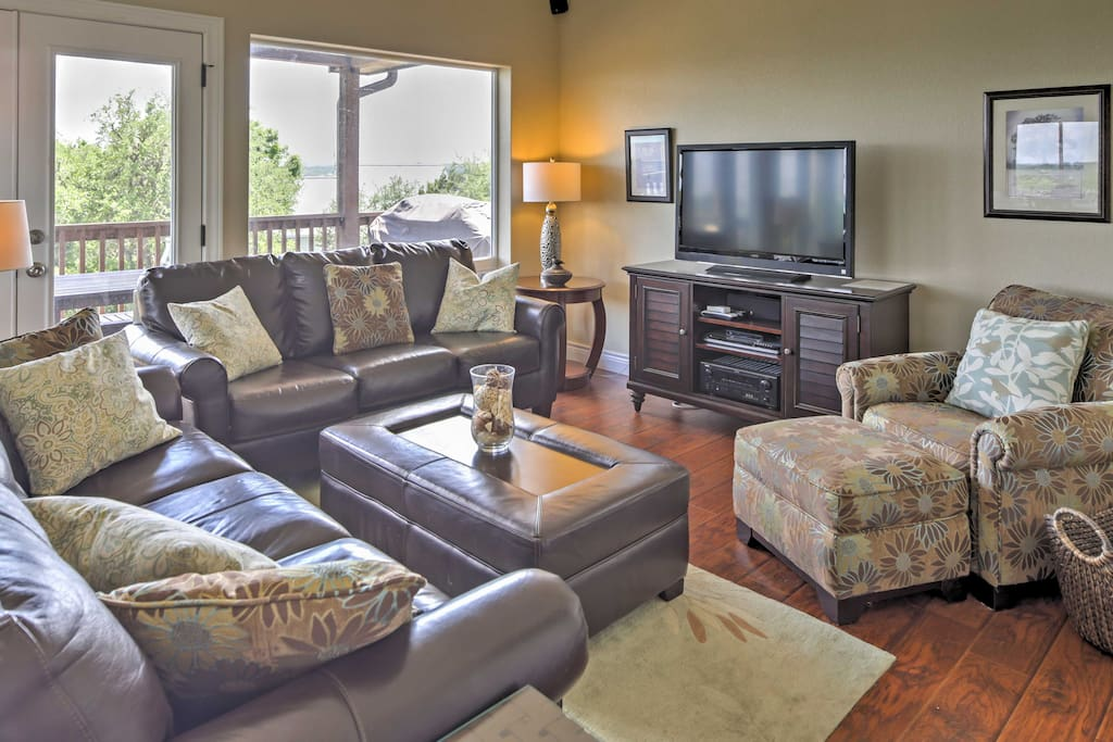 The spacious living room boasts 2 leather sofas, an ottoman and armchair, which surround the entertainment center and flat screen TV!