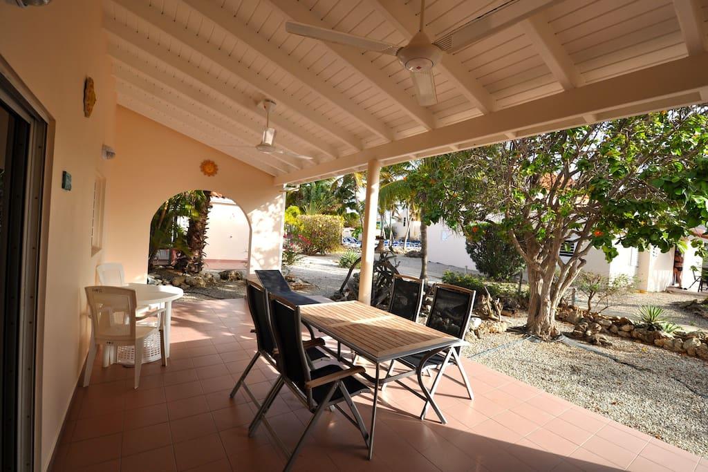 groot overdekt terras met luxe meubilair en twee plafondfans