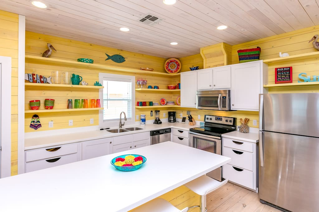 Nautical kitchen with a center island and stainless steel appliances.