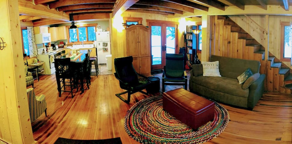 Panorama of 1st floor living room, kitchen, and double doors to back deck