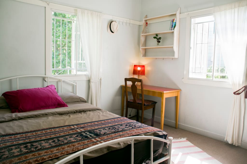 The airy bedroom has a study desk and looks out onto a shady garden.