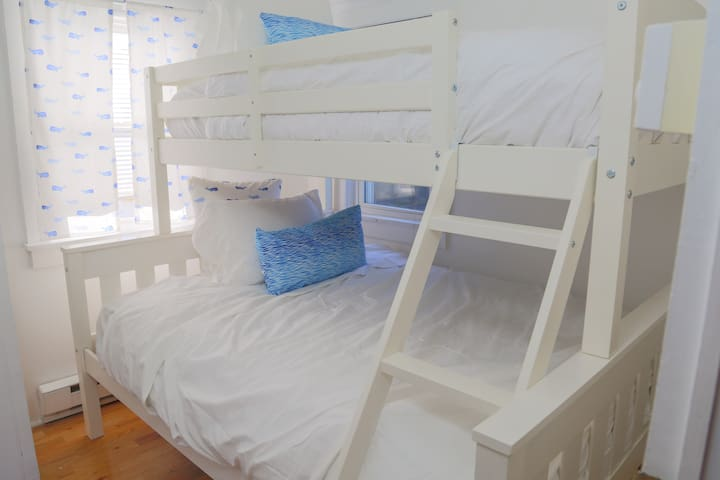 Brand new mattresses and linens on bunk bed.