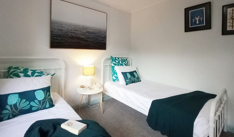 """""""Cosy Corner Room"""" is  an afternoon sunshine filled room. Upstairs looking out to the west, this room is bright and airy with two single beds and large robe."""