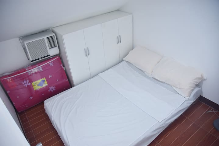 Bedroom 2 with Double Size Sofa Bed together with pillows and bed linens. It is also equipt with an air conditioner, closet, and with an extra bed sheet and pillows.