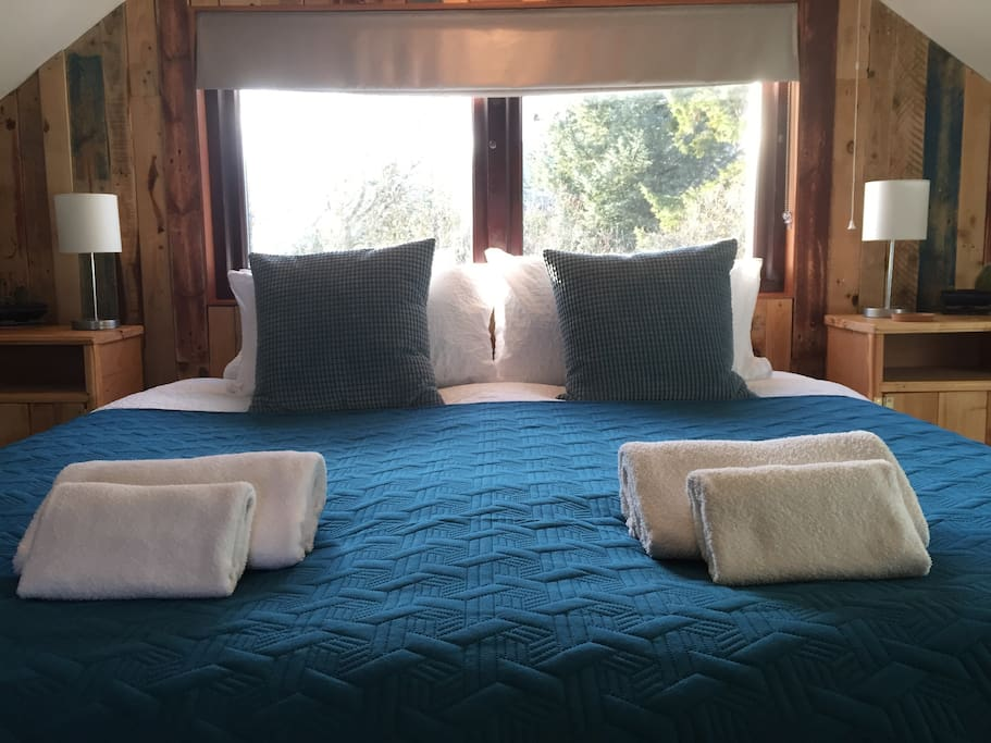 King-sized bed with setting sun behind
