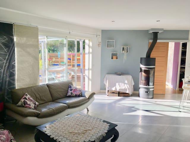 Salon ouvert de 50 m2 avec cuisine ouverte donnant sur la terrasse et la piscine