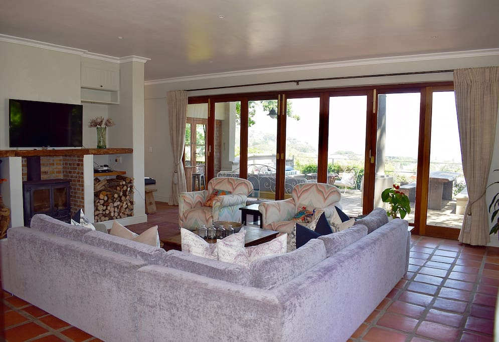 Large lounge, with fireplace, leading onto extensive balcony with stunning sea and mountain views - with braai place and fire pit.