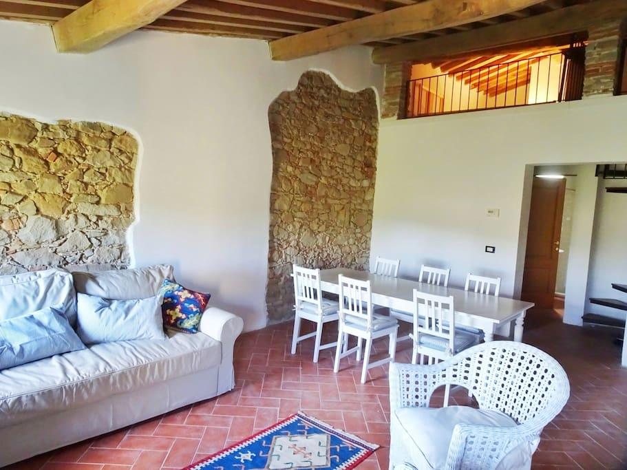 Ampio salone con antico pavimento in cotto e meravigliosa vista sulle colline toscane; divano letto matrimoniale 160x200. In alto il soppalco illuminato con la zona notte.