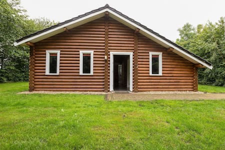 Wooden tree trunk bungalow at fish pond in Hoge Hexel, optional with hot tub