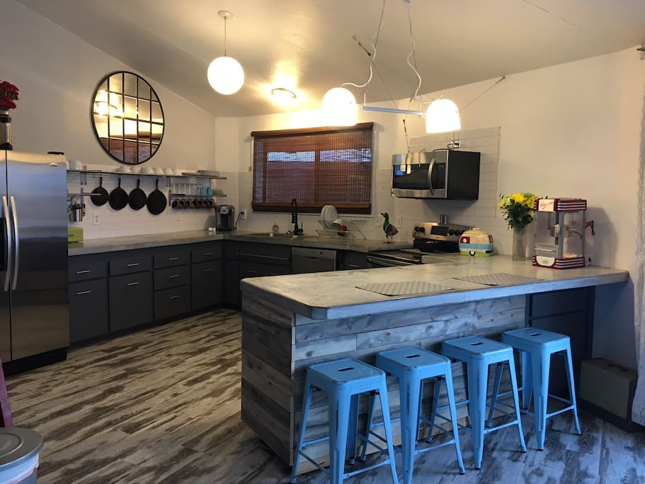 Kitchen with natural concrete countertops, electric range, microwave, fridge with ice maker, eat up bar, large pantry and just about everything you can imagine to cook and eat meals.