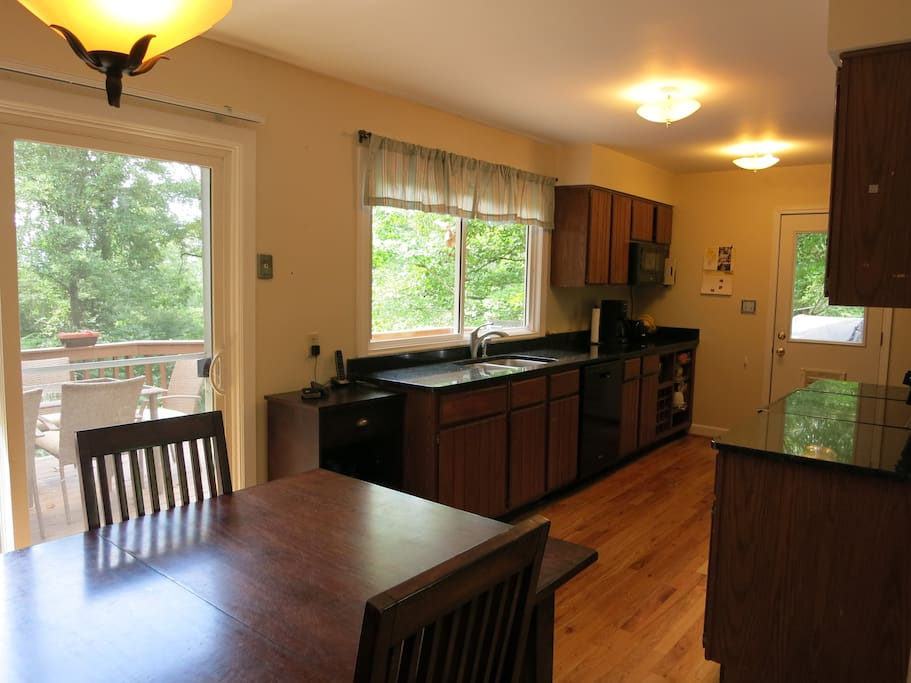 Kitchen with granite countertops and seating for 8 with access to deck.