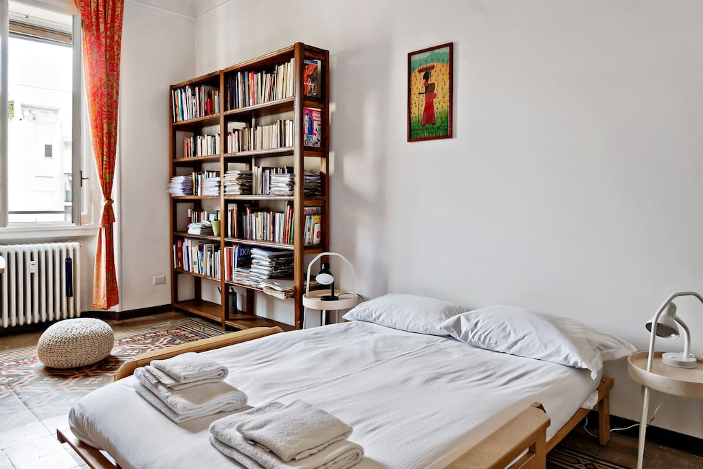 The Bedroom - The comfortable double bed with soft bed-linen and towels & The Bookcase
