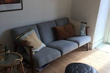 Sofa in the living room, next to the balcony door.