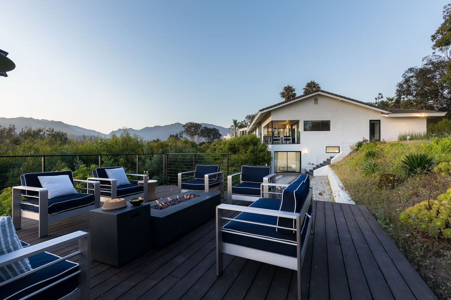 Outdoor patio with ocean and mountain view. Relax around the fire pit!