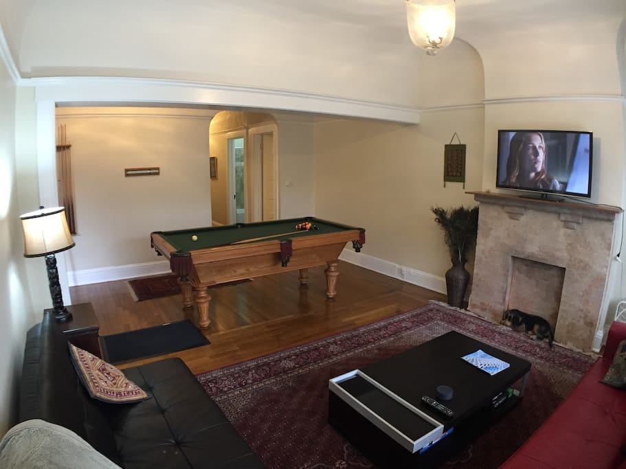 Beautiful, spacious living room with pool table, classic wood floors, wide-screen TV, and 12-foot ceilings. Both  couches fold down to beds if needed.