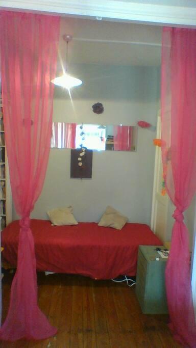 Alcôve dans salon avec lit une place.