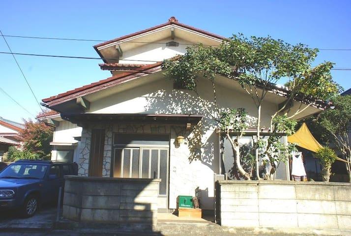 かめハウス外観。 赤い屋根、青い車、緑のポスト、三角形のタープが特徴です。