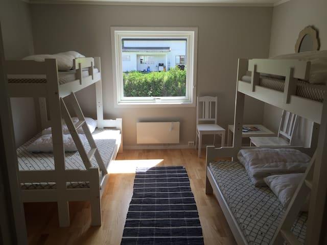 Rommet består av 2 stk familie køyer, 2 stoler, bord, og en liten kommode.