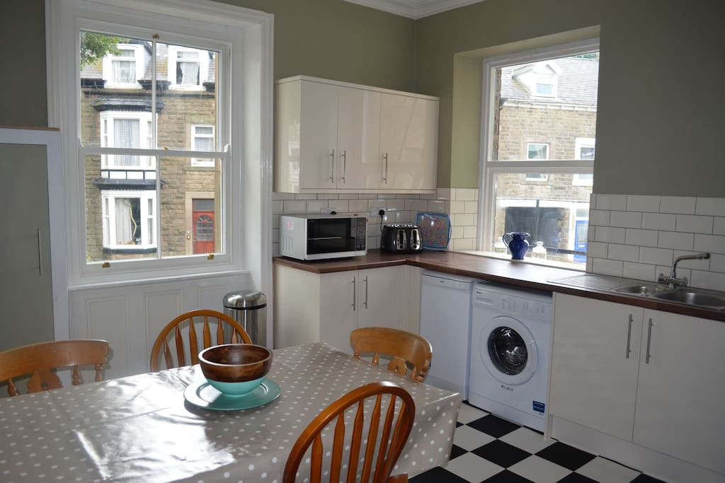Large kitchen with dining table that easily seats six, washing machine, dishwasher, microwave, toaster, kettle, fridge freezer, electric oven and hob.