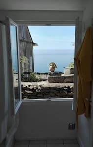 Maisonnette blanche et simple avec vue sur mer.