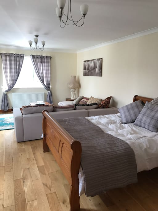 Large open plan area featuring king size bed and sitting area