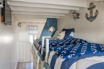 Nautical room with personal touches such as smart TV and USB ports.
