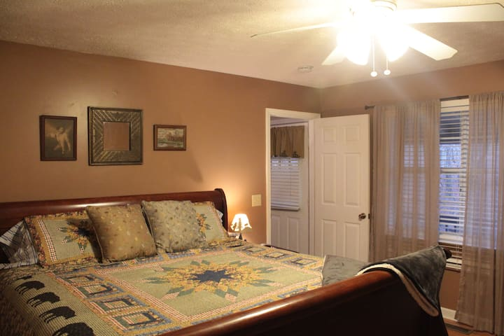 This is the master bedroom, complete with a king-sized bed, a full bath, hard-wood floors, a closet, and adorable cabin decor.