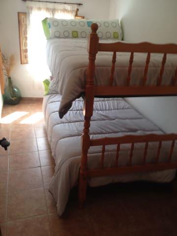 Habitación de niños con dos camas en litera, el acceso a este cuarto es por el dormitorio principal
