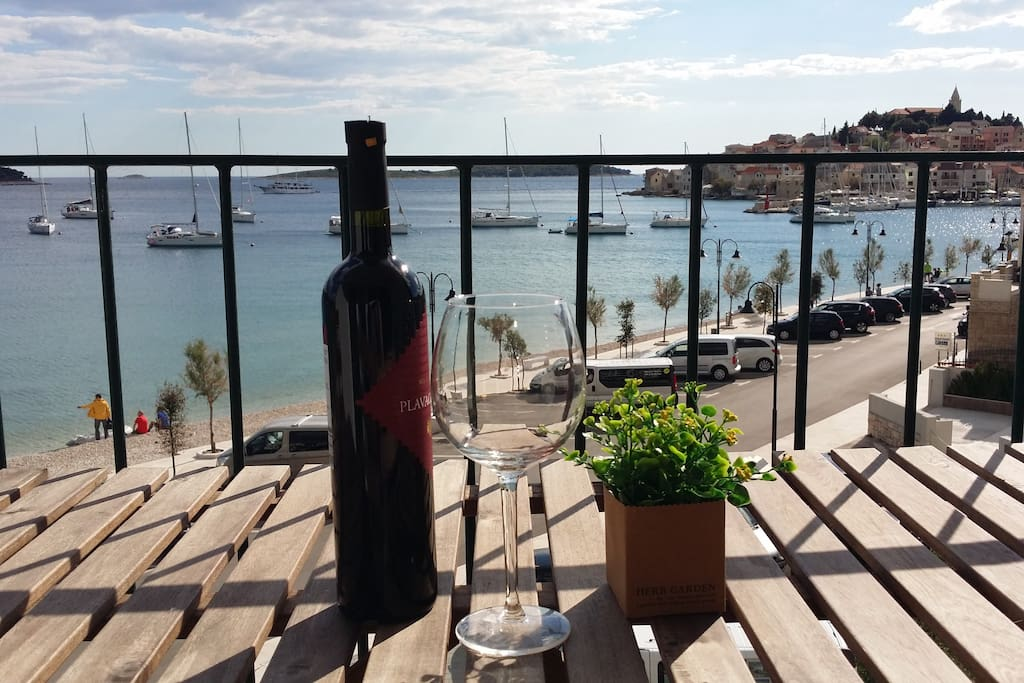 Enjoy a glass of wine on the terrace overlooking the beach and the Old town