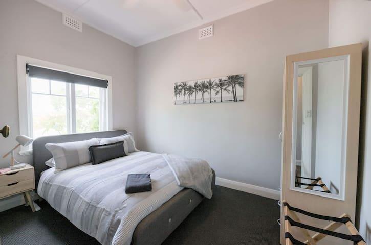 Queen bedroom with storage & garden views.