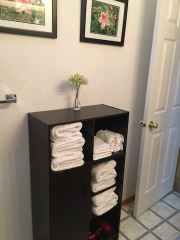 Bathroom includes extra linens, hair dryer, and shower supplies
