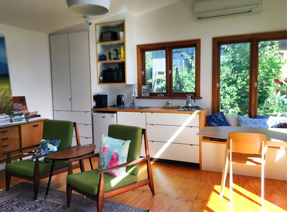 Kitchen area (includes fridge, microwave, kettle, toaster, stovetop, coffee machine) table and cupboard with hanging space and drawers